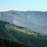 Krähe, die über die Hügel fliegt Lizenzfreies Stockfoto