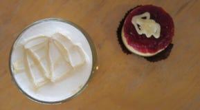 Kräm av den varma kaffe och kakan på trätabellen, nolla för selektiv fokus Arkivbild
