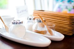 Kräm för kaffe med vitt och rött socker i en exponeringsglaskrus med trämagasin på hyllor arkivfoto