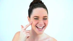 Kräm för skönhet för brunettkvinna fördelande på hennes kind stock video