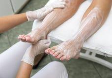kräm- fot kvinnlighänder som moisturizing behandling Arkivbilder