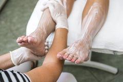 kräm- fot kvinnlighänder som moisturizing behandling Arkivfoto