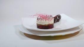 Kräm- kaka med tre lager på en platta Kräm- kaka med tre lager som dekoreras med chokladsmulor och choklad Arkivfoto