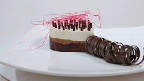Kräm- kaka med tre lager på en platta Kräm- kaka med tre lager som dekoreras med chokladsmulor och choklad Royaltyfri Bild