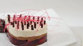 Kräm- kaka med tre lager på en platta Kräm- kaka med tre lager som dekoreras med chokladsmulor och choklad Royaltyfri Fotografi