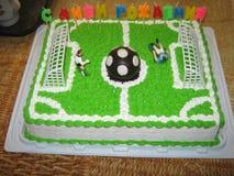 Kräm- kakagrabbfotbollsspelare på hans födelsedag med en boll- och portsötsakefterrätt Royaltyfri Foto