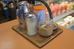 Kräm och socker i glasflaska på coffee shop royaltyfri bild