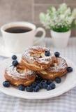 Kräm- puffs eller chouxbakelse ringer med blåbär på plattan Royaltyfria Foton