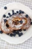 Kräm- puffs eller chouxbakelse ringer med blåbär på plattan Arkivbild