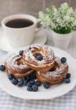 Kräm- puffs eller chouxbakelse ringer med blåbär på plattan Royaltyfria Bilder
