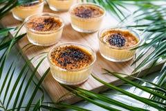Kräm som var brulee på trämagasinet, dekorerade med palmblad Kräm- efterrätt för traditionell fransk vanilj med caramelised socke arkivfoton