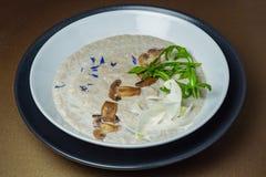 Kräm- soppa för champinjon med den svarta tryffeln i en keramisk vit bunkenolla Royaltyfri Fotografi