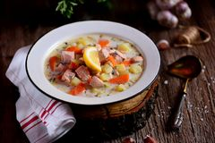 Kräm- soppa för finska med laxen, potatisar och morötter i en gammal tappningplatta på en träbakgrund Lantlig mat, lantlig stil royaltyfria foton