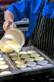 KrämBrule för kock hällande blandning över tenn- former Arkivbild