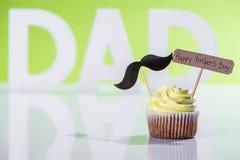 krämig muffin med mustaschtecknet och lycklig inskrift för faderdag framme av farsainskriften som göras av vita bokstäver royaltyfri bild