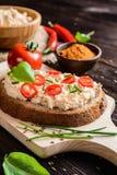 Krämig ostmassaspridning med chili, jordspiskummin, gräslöken och basilika royaltyfri foto