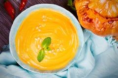 Krämig pumpa- eller butternutsquashsoppa i en bunke, hel grillad pumpa på träbakgrund Royaltyfri Fotografi