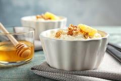 Krämig risgrynsgröt med valnötter och orange skiva i ramekin royaltyfri fotografi