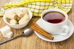 Krämiga godisstänger, kopp te, kanel, socker och tesked Royaltyfri Bild