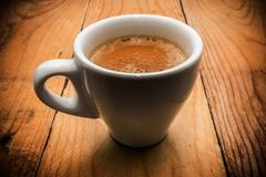 Krämigt kaffe i den vita koppen arkivfoto