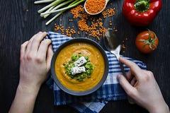 Krämsoppa för den röda linsen dekorerade med nya grönsaker och örter En man ?ter soppa Veggiebegrepp Riktig n?ring royaltyfria foton