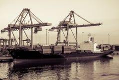 Kräne in anhebenden Behältern des Hafens auf Schiff Stockfotos