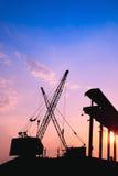 Kräne, die am Sonnenuntergang arbeiten stockfotografie