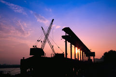 Kräne, die am Sonnenuntergang arbeiten Stockfotos