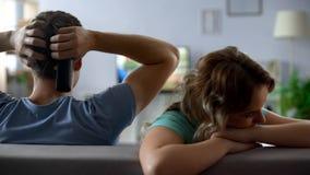 Kränkt flickasammanträde av hållande ögonen på fotbollsmatchtv för pojkvän, förbindelsekris arkivfoto