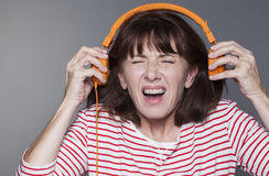 Kränkt 50-talkvinna som tar bort hörlurar från hennes öron Arkivfoto