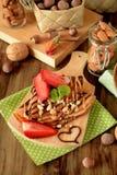 Kräppar dekorerade med muttrar, choklad, nya jordgubbar och mintkaramellen Royaltyfria Bilder