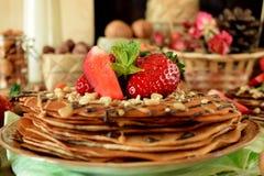 Kräppar dekorerade med muttrar, choklad, nya jordgubbar och mintkaramellen Arkivfoto