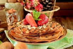 Kräppar dekorerade med muttrar, choklad, nya jordgubbar och mintkaramellen Royaltyfri Bild