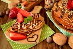 Kräppar dekorerade med muttrar, choklad, nya jordgubbar och mintkaramellen Arkivbild