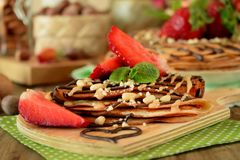 Kräppar dekorerade med muttrar, choklad, nya jordgubbar och mintkaramellen Arkivfoton