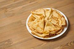 Kräppcloseup, hög av tunna pannkakor på en maträtt, wood bakgrund arkivfoto
