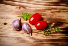 Kräuter und Gemüse auf einem neuen gebrannten hölzernen Hintergrund getont Stockfoto