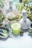 Kräuterbadekurort, Wellness- und Massageeinstellung mit grünen Blumen und Kräuter, Kerze und Körperhautpflegezubehör stockbilder