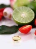 Kräutermedizin-Ölpillen auf Gemüsehintergrund Stockfoto