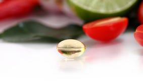 Kräutermedizin-Ölpillen auf Gemüsehintergrund Lizenzfreie Stockfotos