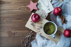 Kräutertee in einer Metallschale und Äpfel auf einem hölzernen braunen backgroun stockfoto