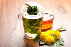Kräutertee mit grünem Löwenzahnblatt in der Teeschale, -honig und -blüten auf Holztisch Stockbilder