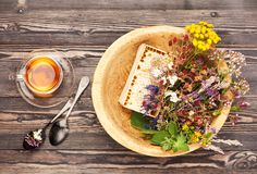 Kräuterteeschale, heilende Kräuter und Honig in einer hölzernen Schüssel auf einem Holztisch Stockbild