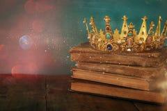 królowa, królewiątko korona na starej książce/ Rocznik filtrujący fantazja średniowieczny okres fotografia stock