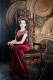Królowa w czerwieni sukni obsiadaniu na tronie piłek władzy przerwy symbolu słowo Zdjęcie Stock