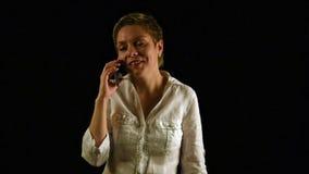 Krótkiego włosy dziewczyna opowiada telefonem komórkowym nad czernią zbiory