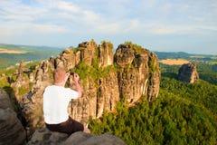 Krótkiego włosy mężczyzna na falezie rockowy i bierze fotografię mądrze telefonem krajobrazowy bellow Słoneczny dzień w skalistyc Obrazy Stock