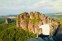Krótkiego włosy mężczyzna na falezie rockowy i bierze fotografię mądrze telefonem krajobrazowy bellow Słoneczny dzień w skalistyc Zdjęcie Royalty Free