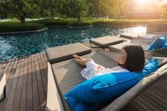 Krótkiego włosy młoda kobieta jest odpoczynkowa przy basenu łóżkiem Zdjęcie Stock