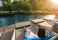 Krótkiego włosy młoda kobieta jest odpoczynkowa przy basenu łóżkiem Zdjęcia Royalty Free